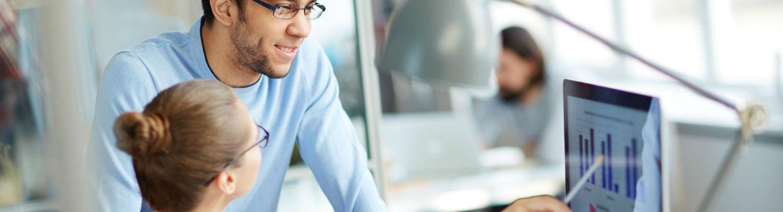 Deux professionnels échangent sur un projet devant un ordinateur